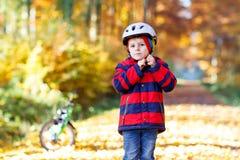 Niño activo que pone el casco seguro antes de completar un ciclo en día soleado de la caída en naturaleza foto de archivo