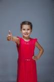 Niño adolescente de la muchacha en el vestido rojo que muestra los pulgares para arriba Fotografía de archivo