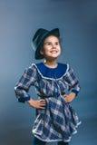 Niño adolescente de la muchacha en un vestido de la tela escocesa y el sombrero de los hombres Imagenes de archivo
