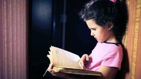 Niño adolescente de la muchacha que lee un libro mientras que se coloca metrajes