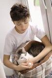 Niño adolescente del muchacho con el gato en la cama que juega cerca encima de la foto Foto de archivo libre de regalías