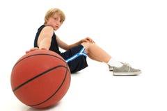 Niño adolescente del muchacho en el uniforme que se sienta con baloncesto Fotos de archivo