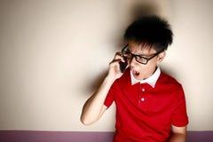 Niño adolescente enojado que habla en un smartphone Imagen de archivo libre de regalías