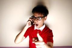 Niño adolescente enojado que habla en un smartphone y que señala en la cámara Fotos de archivo