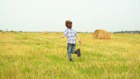 Niño adolescente huyendo en campo otoñal en el campo rural. Ver al chico adolescente corriendo en el campo de cosecha en pajar almacen de video