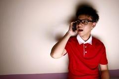 Niño adolescente que habla en un smartphone Foto de archivo libre de regalías