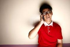 Niño adolescente que habla en un smartphone y una sonrisa Imagen de archivo