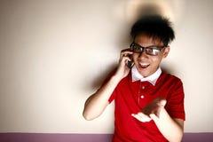Niño adolescente que habla en un smartphone y una sonrisa Fotografía de archivo