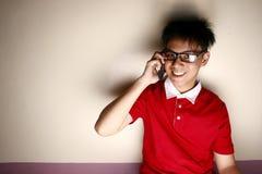 Niño adolescente que habla en un smartphone y una sonrisa Imágenes de archivo libres de regalías