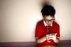 Niño adolescente usando un smartphone Fotografía de archivo