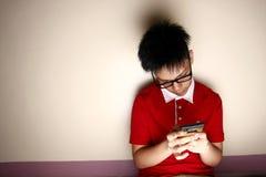 Niño adolescente usando un smartphone Imágenes de archivo libres de regalías