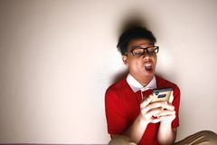 Niño adolescente usando un smartphone intenso Fotografía de archivo libre de regalías