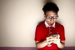 Niño adolescente usando un smartphone y la actuación sorprendido Imagen de archivo
