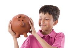 Niño adorable con el moneybox imagen de archivo