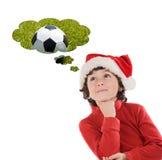 Niño adorable con el sombrero de la Navidad que piensa con un balón de fútbol Fotos de archivo