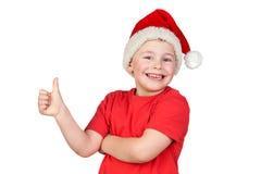 Niño adorable con el sombrero de Santa que dice OK Imagen de archivo libre de regalías