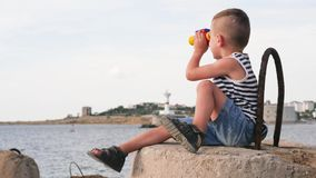 Niño adorable con los prismáticos en la costa que se sienta en bloque del rompeolas almacen de video