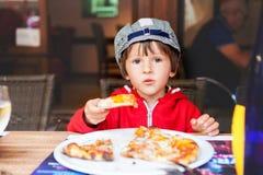 Niño adorable dulce, muchacho, comiendo la pizza en un restaurante fotografía de archivo