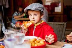 Niño adorable dulce, muchacho, comiendo la pizza en un restaurante fotos de archivo libres de regalías