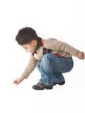 Niño adorable en estudio que se agacha Foto de archivo libre de regalías