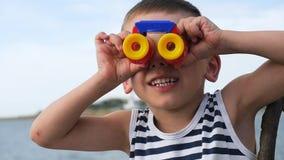 Niño adorable en la camisa rayada que mira a través de los prismáticos delante del horizonte de mar metrajes