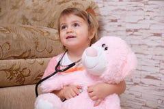 Niño adorable que juega el doctor o a la enfermera con los juguetes de la felpa en casa foto de archivo libre de regalías