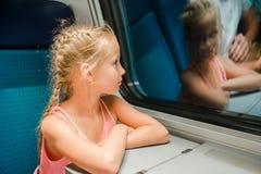 Niño adorable que mira hacia fuera la ventana del tren afuera, mientras que él que se mueve Foto de archivo