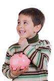 Niño adorable que piensa qué comprar con su sav Fotos de archivo