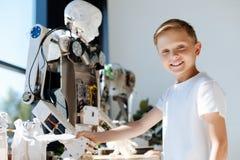 Niño adorable que sacude las manos con el robot humano Fotos de archivo