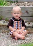 Niño adorable que se sienta en el jardín Foto de archivo libre de regalías