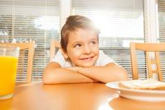 Niño adorable que se sienta en la cocina en el desayuno Foto de archivo libre de regalías