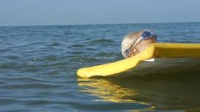 Niño adorable sonriente que goza de bodyboard surfboarding del mar azul Cámara lenta almacen de metraje de vídeo