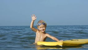Niño adorable sonriente que goza de bodyboard surfboarding del mar azul Cámara lenta metrajes