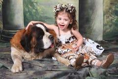Niño adorable y su perro de perrito de St Bernard Foto de archivo
