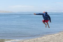 Niño aerotransportado después de saltar apagado de la duna de arena imagenes de archivo