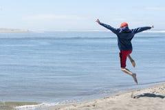 Niño aerotransportado después de saltar apagado de la duna de arena imagen de archivo libre de regalías