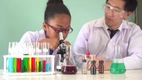 Niño afroamericano asiático del científico enseñando a cómo utilizar el microscopio en sala de clase de la ciencia almacen de video