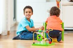 Niño afroamericano de los hermanos que juega junto Foto de archivo