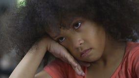 Niño afroamericano triste que se sienta en casa y que piensa en su propio comportamiento metrajes