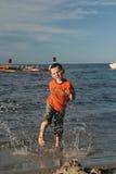 Niño, agua y diversión. Diversión de la playa. Imagenes de archivo