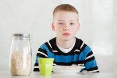 Niño al lado del tarro de la avena, de la taza y del cuenco en la tabla Foto de archivo