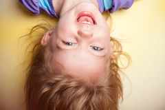 Niño al revés contra fondo amarillo Foto de archivo libre de regalías
