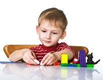 Niño alegre con plasticine fotografía de archivo