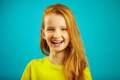 Niño alegre con sonrisa sincera aislado en fondo azul La muchacha pelirroja hermosa lleva la camiseta amarilla, expresa imágenes de archivo libres de regalías