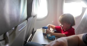 Ni?o alegre que juega con los juguetes durante vuelo almacen de metraje de vídeo