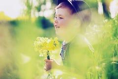 Niño alegre que juega en el prado Foto de archivo