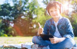 Niño alegre que manosea con los dedos para arriba mientras que escucha la música Fotografía de archivo
