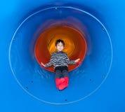 Niño alegre que resbala en diapositiva del tubo Imagenes de archivo