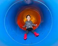 Niño alegre que resbala en diapositiva del tubo Imagen de archivo libre de regalías