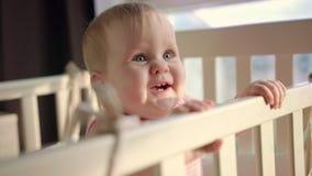 Niño alegre que se coloca en pesebre Niño sonriente que se coloca en cama en casa almacen de metraje de vídeo